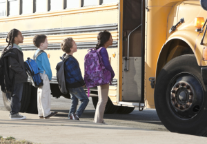 A line of students getting on the school bus.