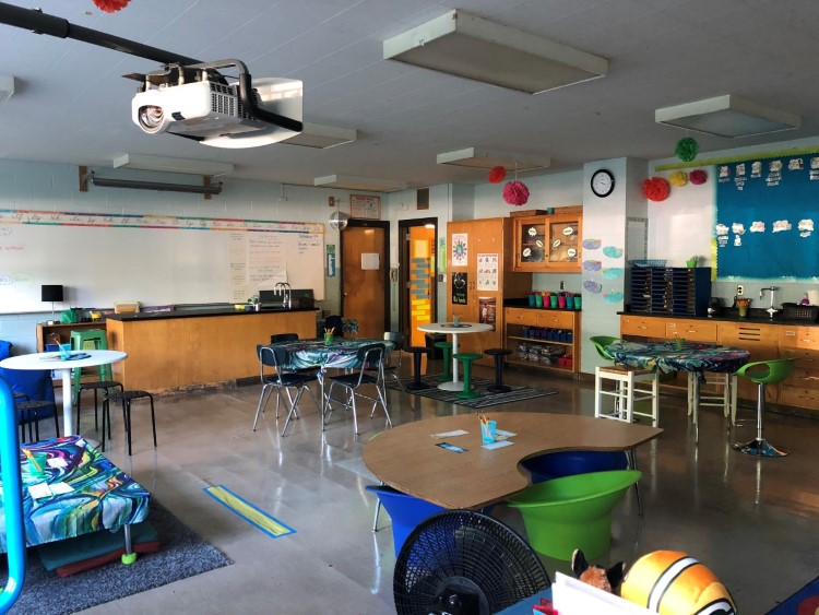 Overall view of classroom with smaller tables that are spaced apart from each other, cabinets, and a large whiteboard.