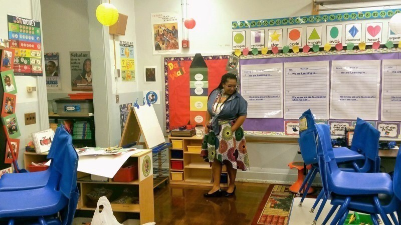 A teacher is standing in front of different activities on bulletins boards, and there are a few stacks of blue chairs.