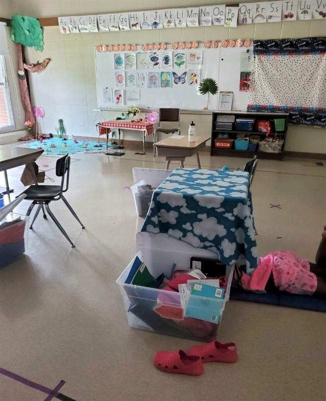 Classroom with a small table that has a blanket draped over it and a large bin filled with notebooks next to it