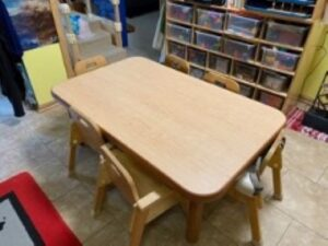 Table with small chairs and shelves nearby filled with bins