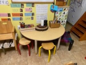 Semicircle table next to a wall with 2 small stools