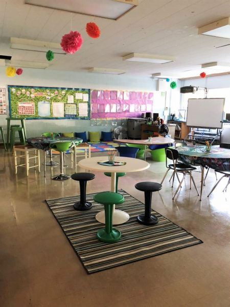 Classroom with different types of seating areas. In the foreground is a circular table with four stools.